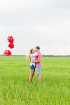 Heureux couple amoureux tenant un ballon rouge dans la nature.