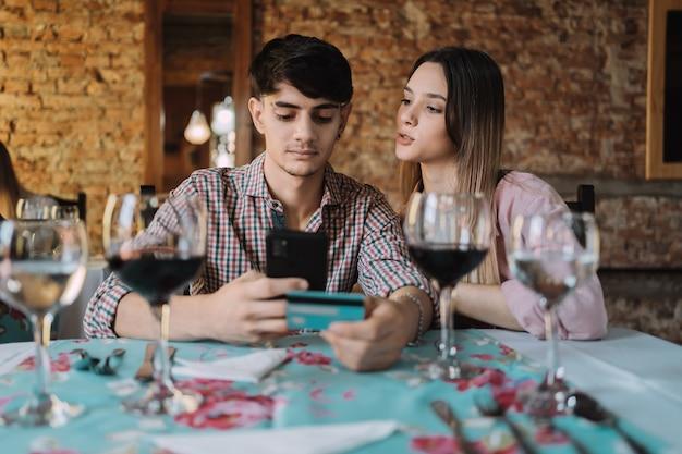 Heureux couple appréciant le dîner et payer la facture avec une carte de crédit