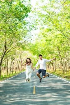 Heureux couple asiatique amoureux sur route avec arche d'arbre