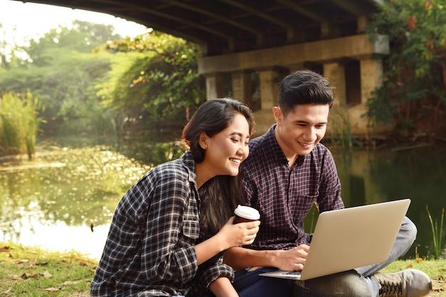Heureux couple asiatique assis et surfer sur le net ensemble