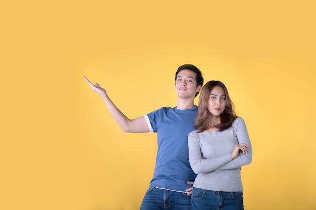 Heureux couple asiatique montrant et présentant un espace de copie dans les affaires et regardant la caméra sur fond jaune