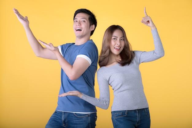 Heureux couple asiatique pointant les doigts vers le haut et regardant la caméra sur fond jaune