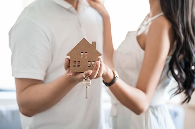 Heureux couple asiatique souriant tenant une maison modèle et dansant avec un sentiment de bonheur. jeune couple d'amoureux avec petite maison en bois nouveau concept de maison