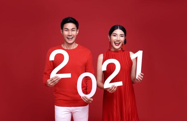Heureux couple asiatique en tenue décontractée rouge montrant 2021 saluant bonne année.