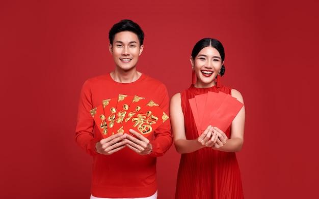 Heureux couple asiatique en tenue décontractée rouge avec tenant angpao ou cadeau monétaire de paquet rouge de félicitations saluant bonne année 2021 sur rouge vif. le texte signifie beaucoup de chance.