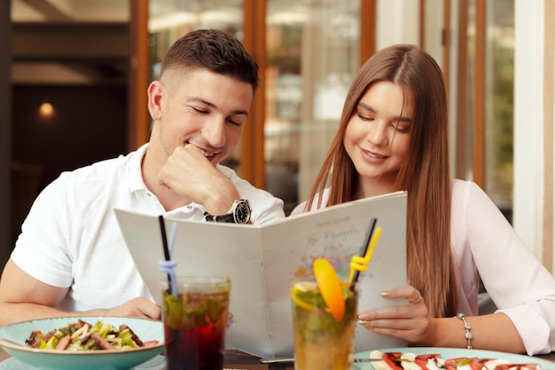 Heureux couple assis au café et regardant le menu