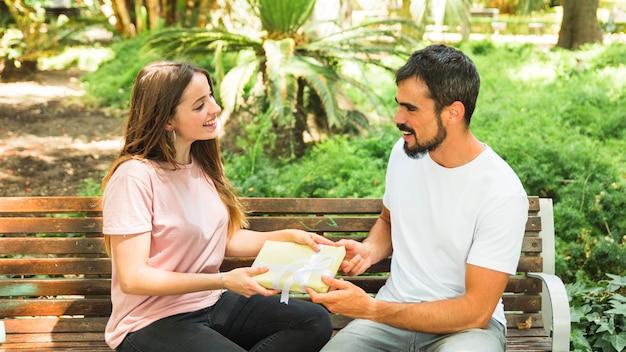 Heureux couple assis sur un banc tenant le cadeau de la saint-valentin