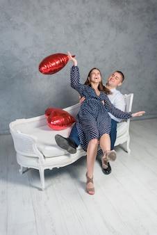 Heureux couple assis sur le canapé avec des ballons coeur