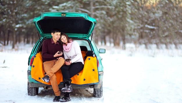 Heureux couple assis dans le coffre ouvert d'une voiture en hiver à l'extérieur avec des tasses de thé chaud dans leurs mains