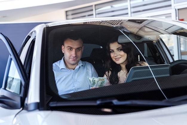 Heureux couple assis dans une nouvelle voiture et souriant