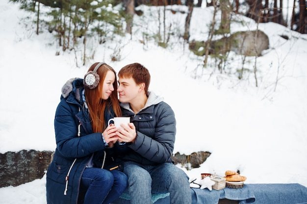 Heureux couple assis à l'extérieur dans la forêt d'hiver, boire des boissons chaudes et se regarder