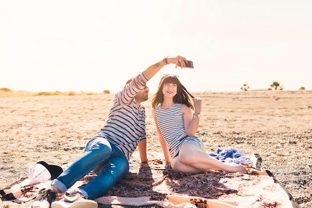 Heureux couple assis sur la plage en tenant autoportrait sur téléphone mobile