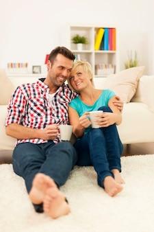 Heureux couple assis sur le sol et boire du café