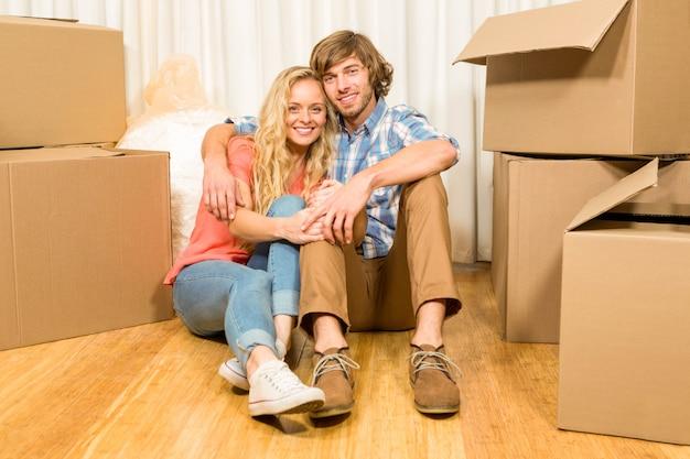 Heureux couple assis sur le sol dans la nouvelle maison