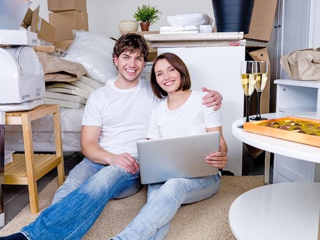 Heureux couple assis sur le sol avec un ordinateur portable après le déménagement