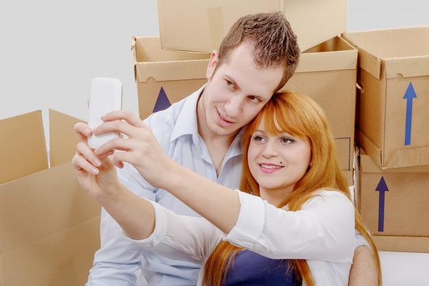 Heureux couple assis sur le sol prenant selfie dans leur nouvelle maison