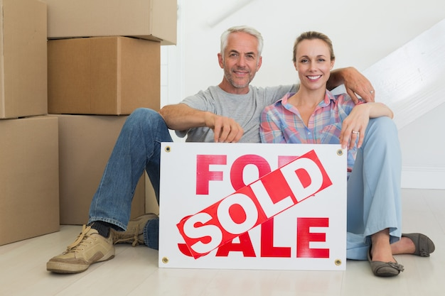 Heureux couple assis sur le sol avec signe vendu