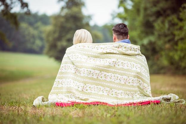 Heureux couple assis sous une couverture à la campagne
