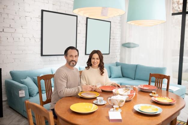 Heureux couple assis à la table dans une pièce lumineuse