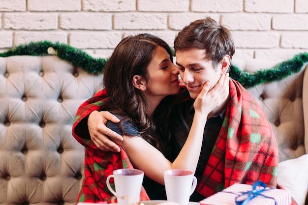 Heureux couple assis avec des tasses de chocolat chaud.