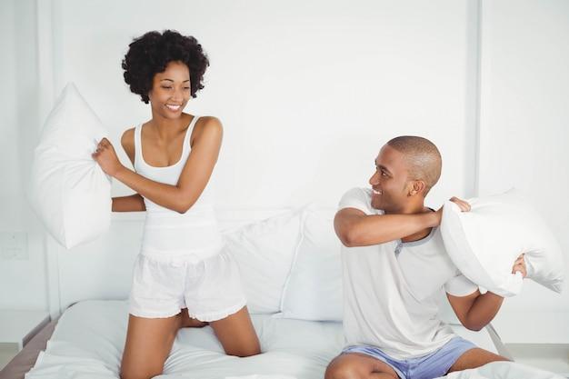 Heureux couple ayant une bataille d'oreillers sur le lit