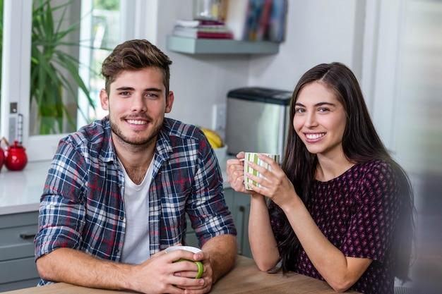 Heureux couple ayant un café ensemble à la maison