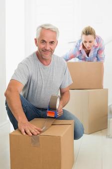 Heureux couple bouge les boîtes de déménagement en carton