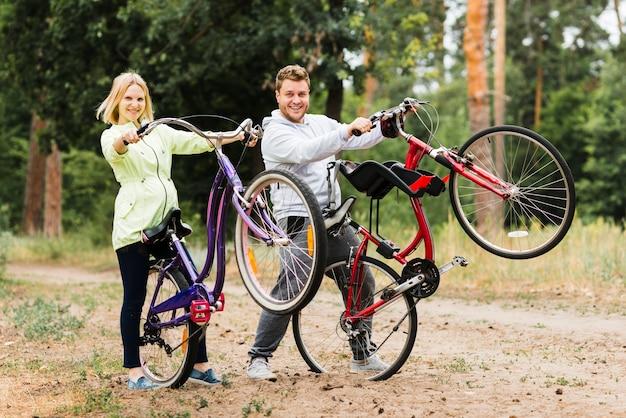 Heureux couple brandissant des vélos