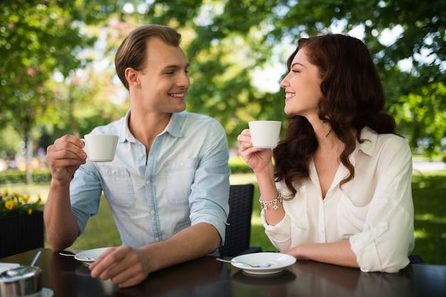 Heureux couple buvant un cappuccino tout en étant assis à l'extérieur