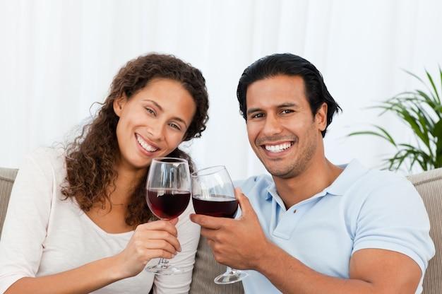 Heureux couple buvant du vin rouge assis sur le canapé