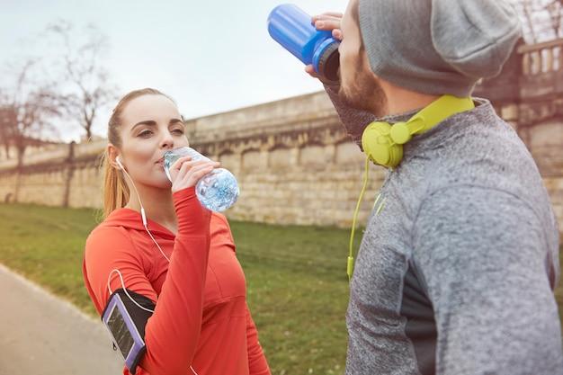 Heureux couple buvant de l'eau après l'exercice