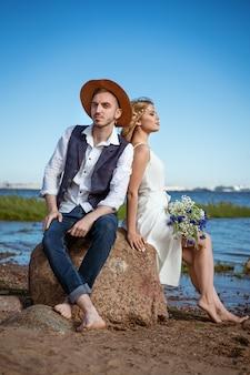 Heureux couple caucasien homme et femme sur la plage journée d'été tenant un bouquet de fleurs à la main
