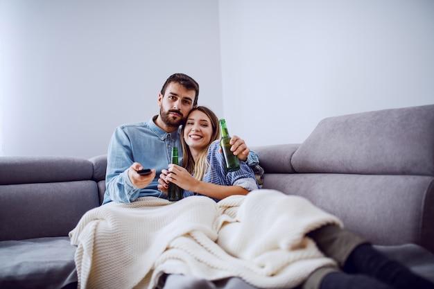 Heureux couple caucasien mignon assis dans le canapé dans le salon, boire de la bière et regarder un film.
