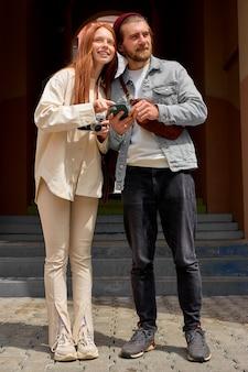 Heureux couple caucasien prenant des photos avec un appareil photo argentique rétro en marchant.