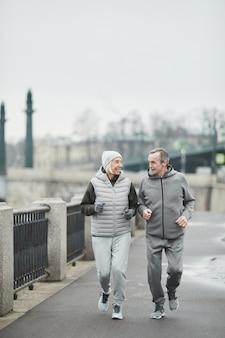 Heureux couple caucasien senior actif en costumes de sport gris discutant et courant le long de la rivière tout en profitant de l'entraînement du matin