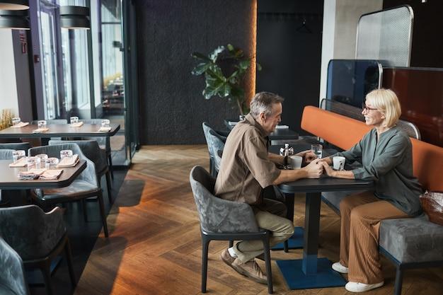 Heureux couple caucasien senior affectueux assis à table et se tenant la main tout en profitant d'un rendez-vous romantique dans un café à la mode