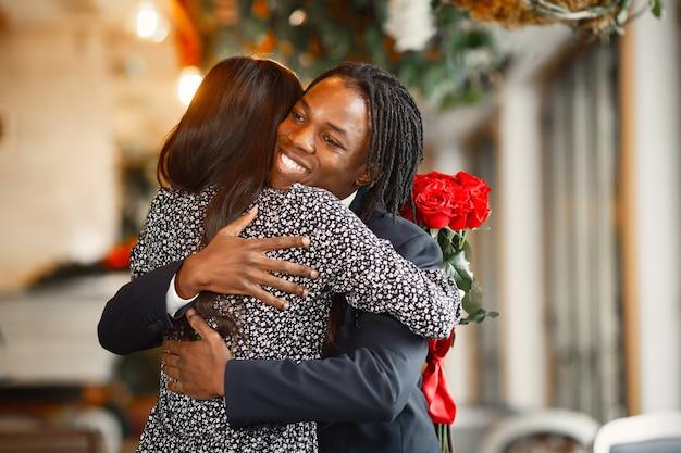 Heureux couple célébrant leurs fiançailles dans un café et serrant étroitement