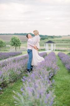 Heureux couple charmant d'âge moyen dans un champ de fleurs de lavande pourpre, passer un moment romantique et célébrer un anniversaire de mariage. l'homme tient sa femme sur les mains et danse