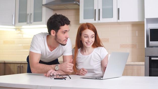 Heureux couple choisit où aller en vacances, regardant un ordinateur portable assis à la maison dans la cuisine