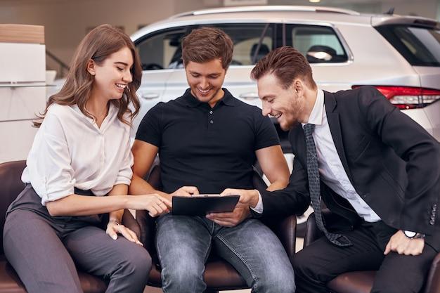 Heureux couple et concessionnaire lisant l'assurance automobile
