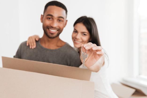 Heureux couple debout avec des boîtes déballées. femme étreignant l'homme. homme tenant une boîte et une clé. en regardant de face. concentrez-vous sur la clé.