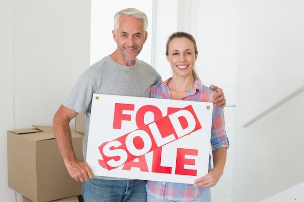 Heureux couple debout et tenant signe vendu