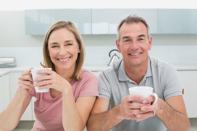 Heureux couple détendu avec des tasses à café dans la cuisine