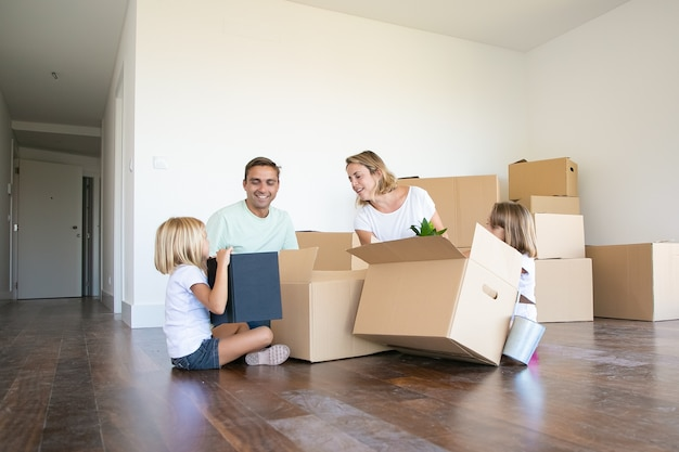 Heureux couple et deux filles emménageant dans un nouvel appartement vide, assis sur le sol près de boîtes ouvertes