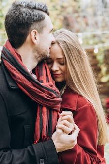 Heureux couple de deux se liant l'un à l'autre pendant la journée confortable dans le parc. homme et femme amoureux datant de la rue d'automne. concept de mode de vie