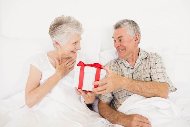 Heureux couple échangeant un cadeau au lit
