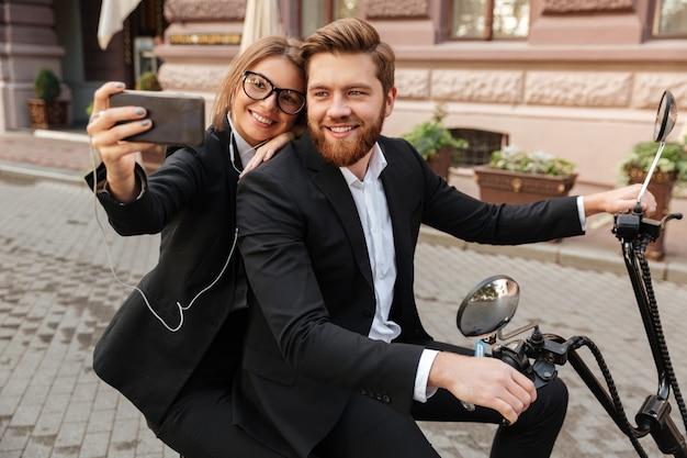 Heureux couple élégant assis sur une moto moderne à l'extérieur