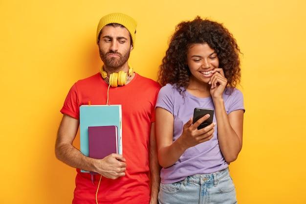Heureux couple élégant posant contre le mur jaune avec des gadgets