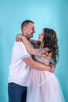 Heureux couple enceinte. beau mari étreignant sa belle femme en studio