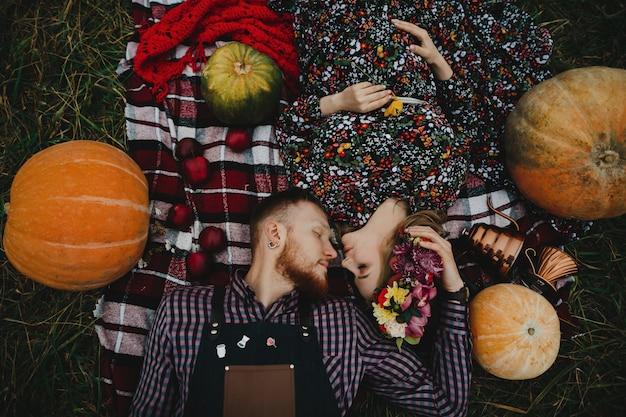 Heureux couple enceinte profite de son temps ensemble allongé sur la loi